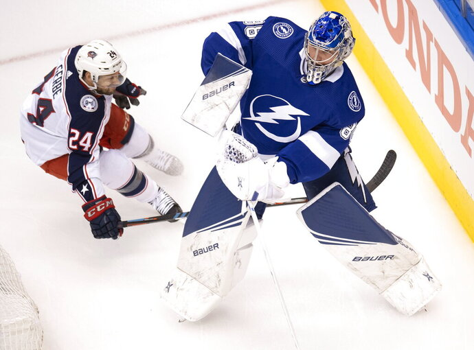 Tampa Bay Lightning goaltender Andrei Vasilevskiy (88) clears the puck under pressure from Columbus Blue Jackets center Nathan Gerbe (24) during the first period in Game 1 of an NHL hockey Stanley Cup first-round playoff series, Tuesday, Aug. 11, 2020, in Toronto. (Frank Gunn/The Canadian Press via AP)