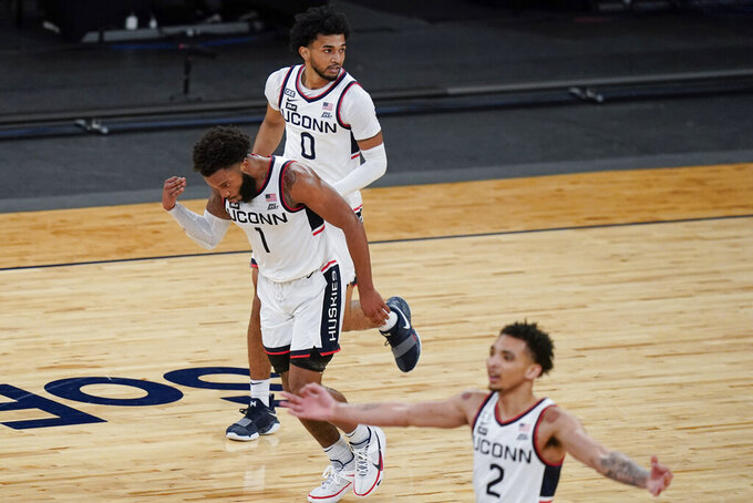 Connecticut's R.J. Cole (1) and James Bouknight (2) celebrate after Cole made a 3-point basket, as Jalen Gaffney (0) looks back during the first half of the team's NCAA college basketball game against DePaul in the Big East mens' tournament Thursday, March 11, 2021, in New York. (AP Photo/Frank Franklin II)