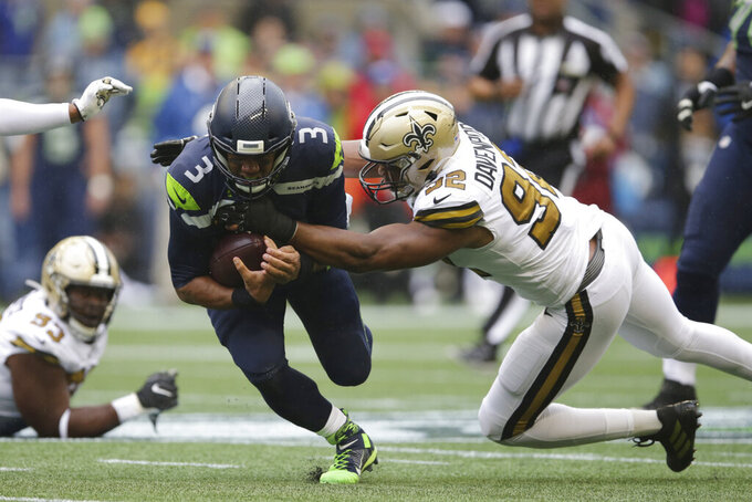 Seattle Seahawks quarterback Russell Wilson (3) is grabbed by New Orleans Saints' Marcus Davenport on a carry during the first half of an NFL football game Sunday, Sept. 22, 2019, in Seattle. (AP Photo/Scott Eklund)