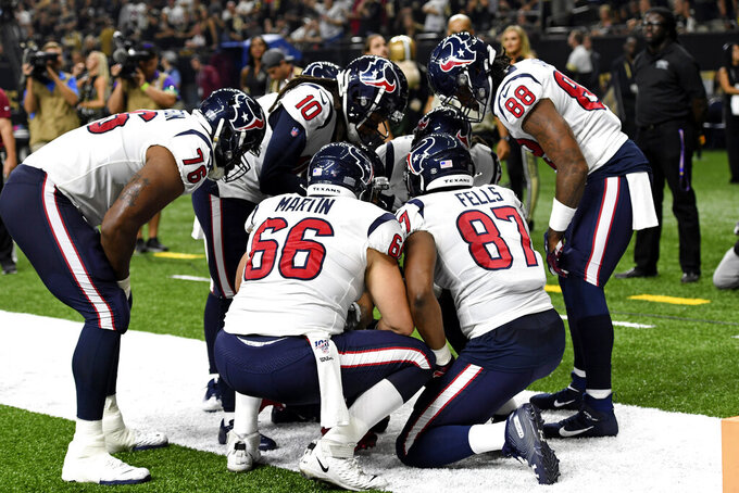 Houston Texans gather around quarterback Deshaun Watson after he hit his head on the turf while diving for a touchdown in the first half of an NFL football game against the New Orleans Saints in New Orleans, Monday, Sept. 9, 2019. (AP Photo/Bill Feig)