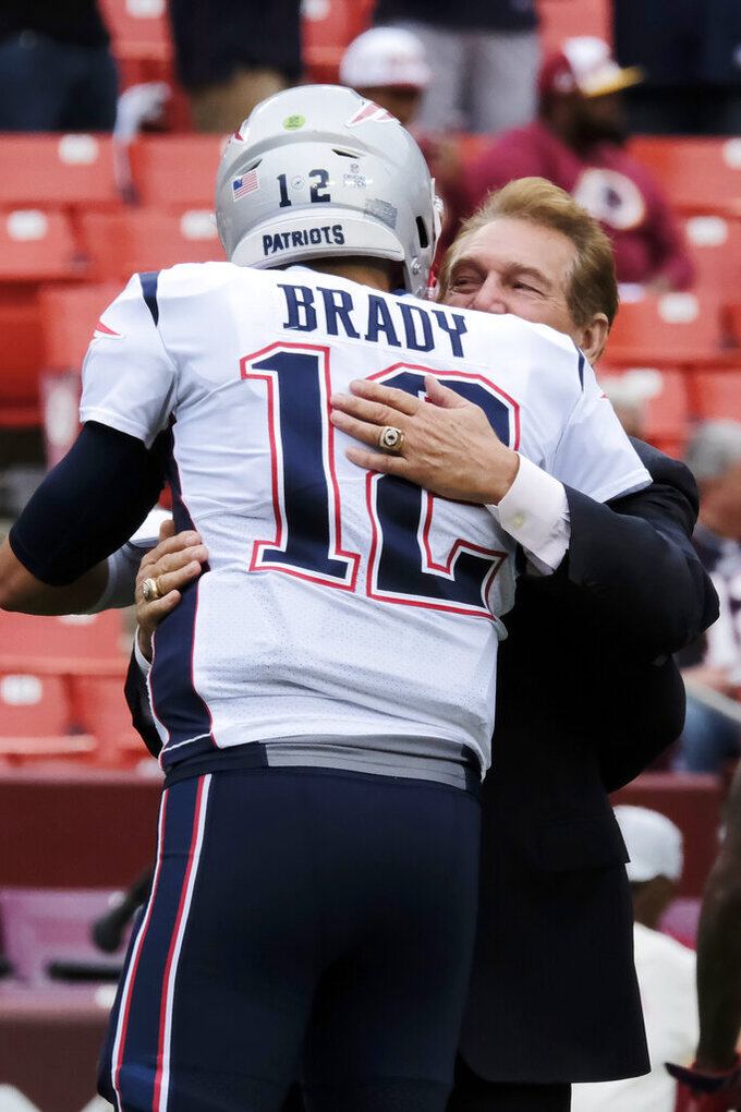 New England Patriots quarterback Tom Brady (12) embraces former NFL player Joe Theismann ahead of an NFL football game between the Washington Redskins and the New England Patriots, Sunday, Oct. 6, 2019, in Washington. (AP Photo/Mark Tenally)