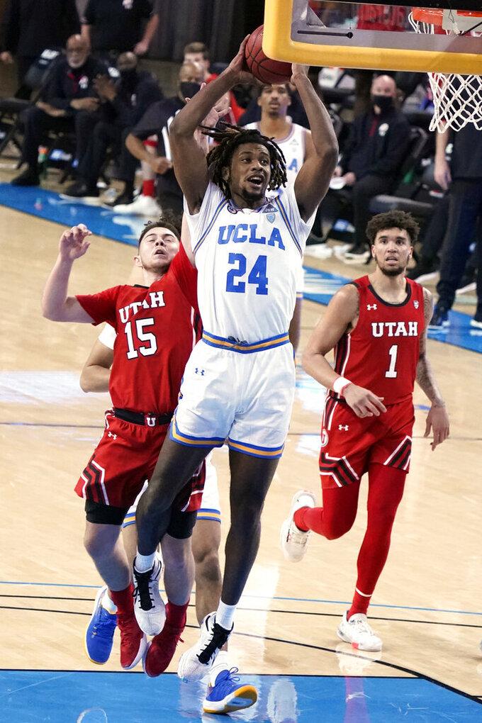 UCLA forward Jalen Hill (24) drives past Utah guard Rylan Jones (15) during the second half of an NCAA college basketball game Thursday, Dec. 31, 2020, in Los Angeles. (AP Photo/Marcio Jose Sanchez)