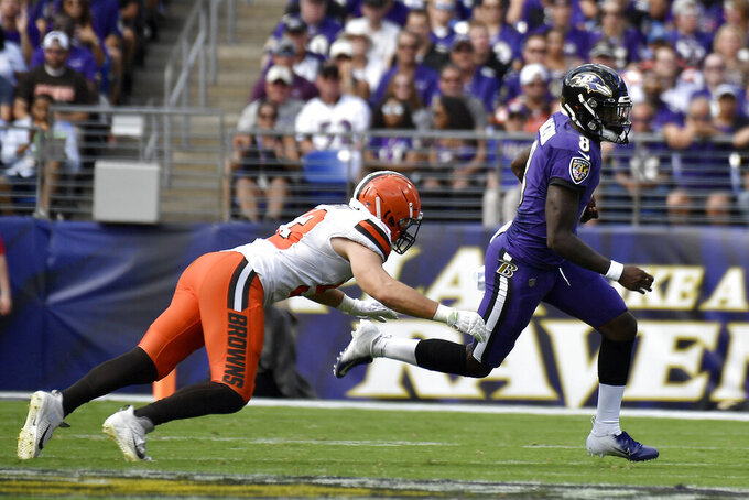 Baltimore Ravens quarterback Lamar Jackson, right, scrambles as Cleveland Browns middle linebacker Joe Schobert pursues during the first half of an NFL football game Sunday, Sept. 29, 2019, in Baltimore. (AP Photo/Brien Aho)