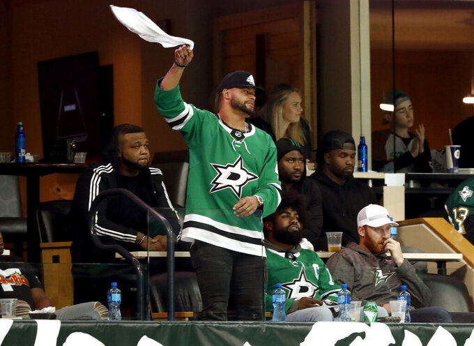 Dallas Cowboys quarterback Das Prescott stands and waves his rally towels as he and running back Zeke Elliott, sitting right, watch in the third period of Game 6 in an NHL hockey first-round playoff series between the Dallas Stars and the Nashville Predators in Dallas, Monday, April 22, 2019. (AP Photo/Tony Gutierrez)