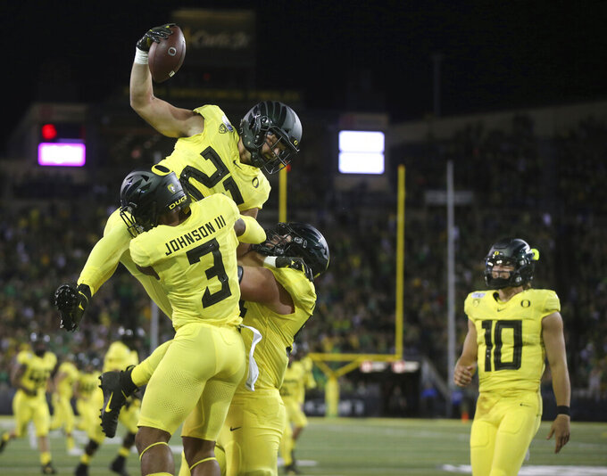 Oregon's Jacob Breeland, top, celebrates a first-quarter touchdown against Montana with teammates, including quarterback Justin Herbert, right, during an NCAA college football game Saturday, Sept. 14, 2019, in Eugene, Ore. (AP Photo/Chris Pietsch)