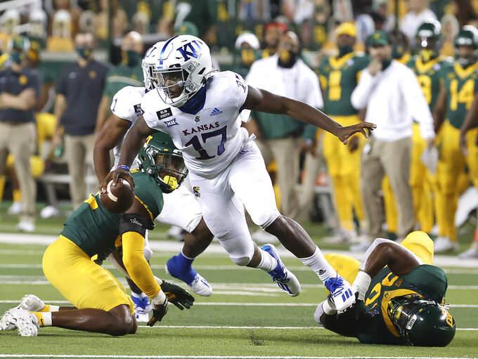 Kansas quarterback Jalon Daniels (17) escapes the tackle by the Baylor defense in the first half of an NCAA college football game in Waco, Texas, Saturday, Sept. 26, 2020. (Jerry Larson/Waco Tribune Herald, via AP)