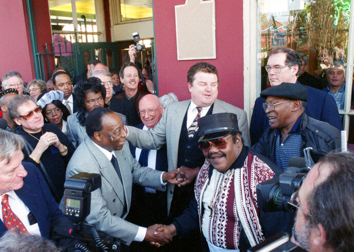 CORRECTS THAT BARTHOLOMEW IS AT LEFT, NOT RIGHT.  - FILE - In a Dec. 10, 1999 file photo, Fats Domino, center right, shakes hands with Dave Bartholomew, left, amid a crowd of former colleagues at the 50th anniversary observance of Domino's first recording session in New Orleans.  Bartholomew, a giant of New Orleans music and a rock n' roll pioneer who with Fats Domino co-wrote and produced such classics as