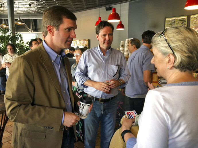 Democratic gubernatorial nominee Andy Beshear, left, speaks with a coffee shop customer on Wednesday, June 29, 2019, in Louisville, Ky., while his former campaign rival, Adam Edelen, center, looks on. Beshear and Edelen appeared together as Democrats put on a united front in their effort to unseat Republican Gov. Matt Bevin in the November election in Kentucky. (AP Photo/Bruce Schreiner)