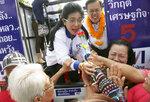 In this March 21, 2019, photo, the leader of Pheu Thai Party and candidate for prime minister Sudarat Keyuraphan, center, meets supporters during an election campaign in Bangkok, Thailand. More than 70 parties are contesting Sunday's general election in Thailand, the first since a military coup nearly five years ago. (AP Photo/Sakchai Lalit)