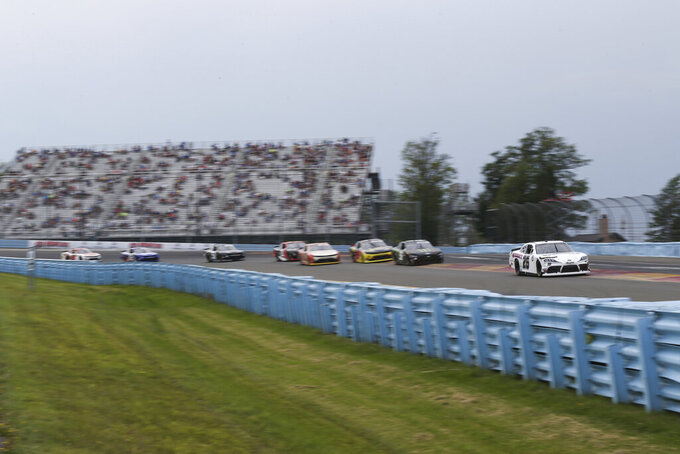 Kris Wright (26) lets a group of cars as they round Turn 1 in the NASCAR Xfinity Series auto race at Watkins Glen International in Watkins Glen, N.Y., on Saturday, Aug. 7, 2021. (AP Photo/Joshua Bessex)