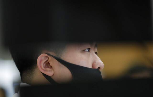 An employee of a bank wearing a face mask watches the computer monitors at the foreign exchange dealing room in Seoul, South Korea, Tuesday, March 31, 2020. Asian shares surged Tuesday after a rally in U.S. stocks, mostly spurred by health care companies' announcements of developments that could aid in the coronavirus outbreak. (AP Photo/Lee Jin-man)