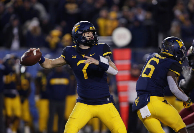 West Virginia quarterback Will Grier (7) looks for a receiver during the first half of an NCAA college football game against Oklahoma on Friday, Nov. 23, 2018, in Morgantown, W.Va. (AP Photo/Raymond Thompson)