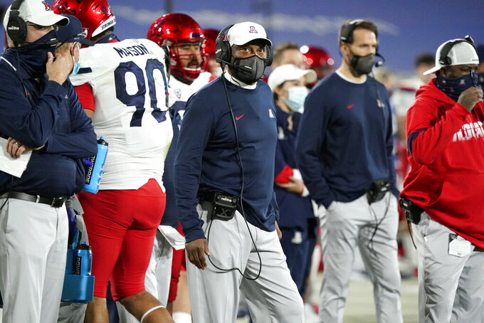Arizona coach Kevin Sumlin, center, watches from the sideline during the first half of the team's NCAA college football game against UCLA on Saturday, Nov. 28, 2020, in Pasadena, Calif. (AP Photo/Marcio Jose Sanchez)