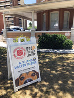 A sign board welcoming people to bring their dogs sits out front at the Salvation Army Phoenix downtown headquarters where a heat relief station was set up on Thursday, May 28, 2020, in Phoenix, Ariz. The heat relief station offering cold water and a cool place inside to rest out of the brutal sun will be open every day through Sunday while an excessive heat warning is in effect. (AP Photo/Anita Snow)