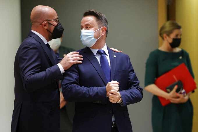 FILE - In this file photo dated Thursday June 24, 2021, European Council President Charles Michel, left, greets Luxembourg's Prime Minister Xavier Bettel during an EU summit at the European Council building in Brussels.  The government of Luxembourg said Monday June 28, 2021, that Prime Minister Xavier Bettel has tested positive for COVID-19 and is in isolation for 10 days. (AP Photo/Olivier Matthys, FILE)