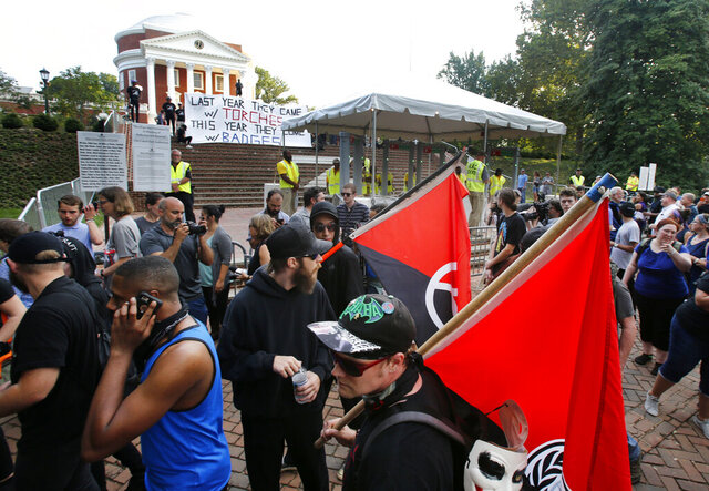 "FILE - In this Saturday, Aug. 11, 2018 file photo, a group of anti-fascist and Black Lives Matter demonstrators march in front of the Rotunda on the campus of the University of Virginia in anticipation of the anniversary of the previous year's Unite the Right rally in Charlottesville, Va. Rutgers University historian Mark Bray, author of the book ""Antifa: The Anti-Fascist Handbook,"" said there are well organized, tightly knit antifa groups that have operated for years. ""But that's different from saying that the politics of antifa is just one single, monolithic organization, which is obviously false,"" said Bray, whose book traces the history and evolution of the movement. (AP Photo/Steve Helber)"