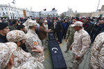 Soldiers stand by the coffins during a funeral of military cadets in Tripoli, Libya, Sunday, Jan. 5, 2020. Health officials said the death toll from the airstrike climbed to at least 30 people, most of them students and over 30 others were wounded. The airstrike took place in the city's south late Saturday, an area which has seen heavy clashes in recent months. Forces based in eastern Libya and led by Gen. Khalifa Hifter have been fighting to seize the capital from the weak but U.N.-supported government. (AP Photo/Hazem Ahmed)