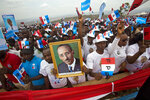 FILE - In this Aug. 2, 2017, file photo, supporters of Rwanda's President Paul Kagame, portrait center, attend an election campaign rally on the hills overlooking Kigali, Rwanda. As Rwanda commemorates the 25th anniversary of the genocide Sunday, April 7, 2019, with yet more somber festivities, Kagame remains a constant figure atop Rwandan politics. (AP Photo/Jerome Delay, File)