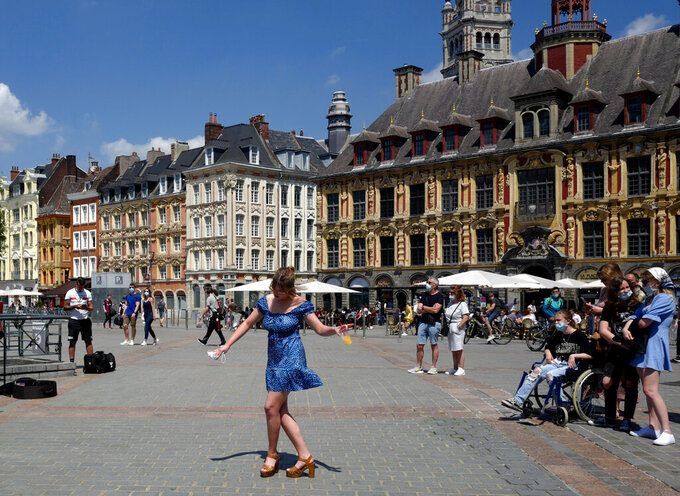 FILE - In this June 6, 2021 file photo, a woman dances by a cafe terrace in Lille, northern France. France is lifting mandatory mask-wearing outdoors and will halt an eight-month nightly coronavirus curfew on June 20.(AP Photo/Michel Spingler, File)