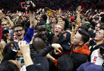 San Diego State forward Aguek Arop, center left, is swarmed by fans after San Diego State defeated Nevada 65-57 in an NCAA college basketball game Wednesday, Feb. 20, 2019, in San Diego. (AP Photo/Gregory Bull)