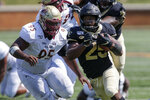 Wake Forest running back Kenneth Walker III, right, runs past Elon defensive lineman Destin Flloyd on his way to scoring a touchdown in the second half of an NCAA college football game in Winston-Salem, N.C., Saturday, Sept. 21, 2019. Wake Forest won 49-7. (AP Photo/Nell Redmond)