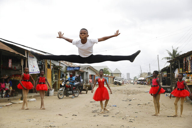 Ballet student Anthony Mmesoma Madu, center, dances in the street as fellow dancers look on in Lagos, Nigeria on Aug. 18, 2020. Cellphone video showing the 11-year-old dancing barefoot in the rain went viral on social media. Madu's practice dance session was so impressive that it earned him a ballet scholarship with the American Ballet Theater in the U.S. (AP Photo/Sunday Alamba)