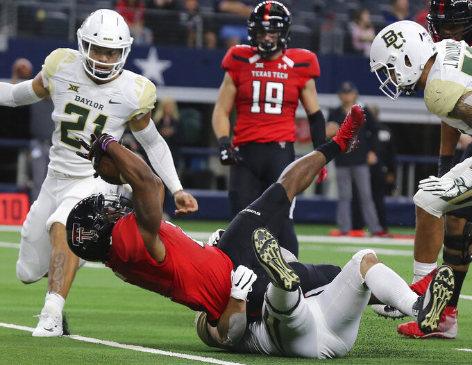 Texas Tech running back Demarcus Felton (2) scores a touchdown against Baylor linebacker Clay Johnston (44) in the first half of an NCAA college football game Saturday, Nov. 24, 201 in Arlington, Texas. (Jerry Larson/Waco Tribune-Herald via AP)