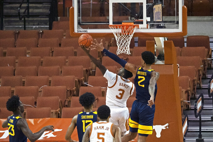 West Virginia forward Jalen Bridges (2) defends a shot by Texas guard Courtney Ramey (3) during the first half of an NCAA college basketball game, Saturday, Feb. 20, 2021, in Austin, Texas. (AP Photo/Michael Thomas)