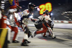 Crew members work a pit stop as Cristopher Bell comes in during a NASCAR Cup Series auto race Sunday, Sept. 5, 2021, in Darlington, S.C. (AP Photo/John Amis)
