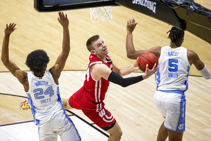 Wisconsin's Brad Davison, center, drives in for a layup between North Carolina's Kerwin Walton (24) and Armando Bacot (5) during the second half of a first-round game in the NCAA men's college basketball tournament, Friday, March 19, 2021, at Mackey Arena in West Lafayette, Ind. (AP Photo/Robert Franklin)