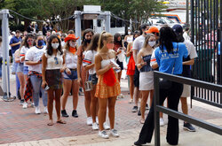 Auburn students are scanned to check for a health screening questionnaire before entering the stadium for the start of an NCAA college football game between Auburn and Kentucky on Saturday, September 26, 2020 in Auburn, Alabama. (AP Photo/Butch Dill)