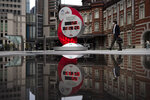 A countdown clock for the Tokyo 2020 Olympics is reflected in a puddle of water outside Tokyo Station in Tokyo, Monday, March 23, 2020. On Tuesday, March 24, Japan and the International Olympic Committee agreed to postpone the Tokyo Olympic Games until the summer of 2021 because of the coronavirus pandemic.(AP Photo/Jae C. Hong)