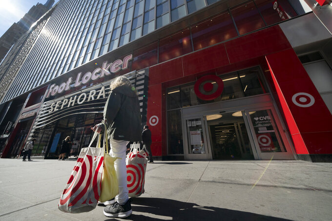 A woman carries Target shopping bags as she leaves the store, Monday, April 19, 2021 in New York. Retail sales in the U.S. were flat in April, after soaring in March, when many Americans received $1,400 stimulus checks that boosted spending. The report from the U.S. Commerce Department was worse than the 0.8% growth Wall Street analysts had expected.    (AP Photo/Mark Lennihan)