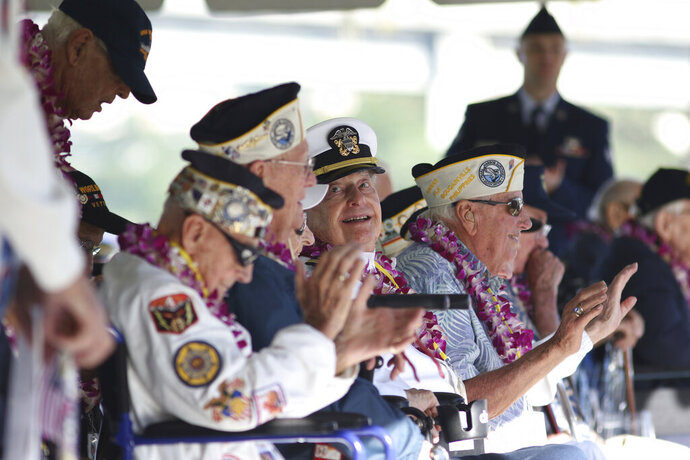 Pearl Harbor survivor Lou Conter, 98, center, who was the only survivor from the USS Arizona to make it to this year's ceremony, smiles during the 78th anniversary of the Japanese attack on Pearl Harbor, Saturday, Dec. 7, 2019 at Pearl Harbor, Hawaii. Survivors and members of the public gathered in Pearl Harbor to remember those killed when Japanese planes bombed the Hawaii naval base 78 years ago and launched the U.S. into World War II. About a dozen survivors of the attack attended the annual ceremony, the youngest of whom are now in their late 90s. (AP Photo/Caleb Jones)