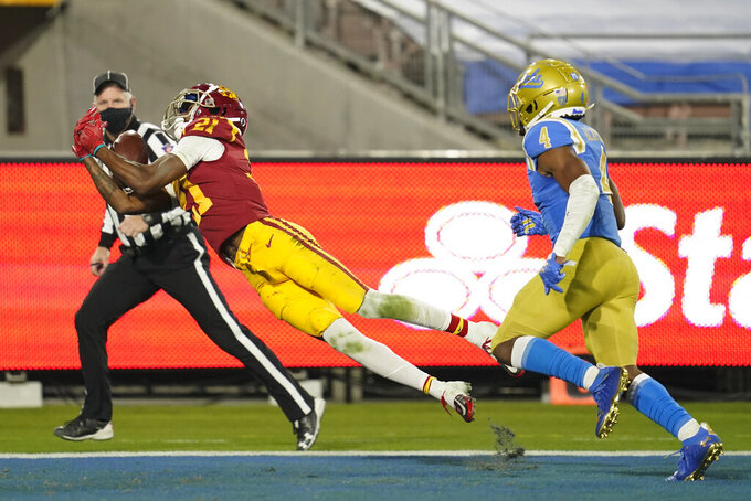 Southern California wide receiver Tyler Vaughns, left, catches a pass in the end zone for a touchdown during the fourth quarter of an NCAA college football game against UCLA, Saturday, Dec 12, 2020, in Pasadena, Calif. UCLA defensive back Stephan Blaylock (4) is at right. (AP Photo/Ashley Landis)