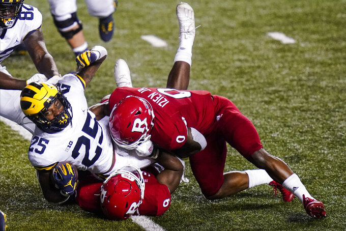 Rutgers' Tyreek Maddox-Williams and Christian Izien, right, tackle Michigan's Hassan Haskins (25) during the third overtime of an NCAA college football game Saturday, Nov. 21, 2020, in Piscataway, N.J. Michigan won 48-42. (AP Photo/Frank Franklin II)
