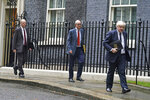 Chief Medical Officer for England Chris Whitty, Chief Scientific Adviser Sir Patrick Vallance and Prime Minister Boris Johnson, from left, leaving 10 Downing Street, London, ahead of a COVID-19 media briefing in the Downing Street Briefing Room, Tuesday Sept. 14, 2021. (Victoria Jones/PA via AP)