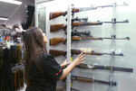 FILE - In this Wednesday, Oct. 4, 2017 file photo, a salesperson checks rifles in a gun shop display in Sydney, Australia. A documentary aired in March 2019 by Al Jazeera reported officials with Australia's far-right One Nation party met with two National Rifle Association representatives and other gun-rights advocates seeking money to undermine Australian gun laws. (AP Photo/Rick Rycroft)