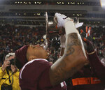 Virginia Tech's Jovonn Quillen tips ice water from the Commonwealth Cup after the team's 34-31 win over Virginia in an NCAA college football game Friday, Nov. 23, 2018, in Blacksburg, Va. (Matt Gentry/The Roanoke Times via AP)