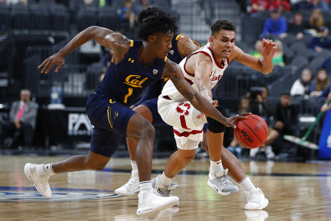 California's Joel Brown (1) dribbles around Stanford's Oscar da Silva (13) during the second half of an NCAA college basketball game in the first round of the Pac-12 men's tournament Wednesday, March 11, 2020, in Las Vegas. (AP Photo/John Locher)