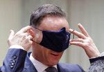 German Foreign Minister Heiko Maas puts on a face mask, to prevent the spread of coronavirus, as he attends an EU foreign ministers at the European Council building in Brussels, Monday, July 13, 2020. European Union foreign ministers meet for the first time face-to-face since the pandemic lockdown and will assess their discuss their relations with China and Turkey. (Stephanie Lecocq, Pool Photo via Ap)