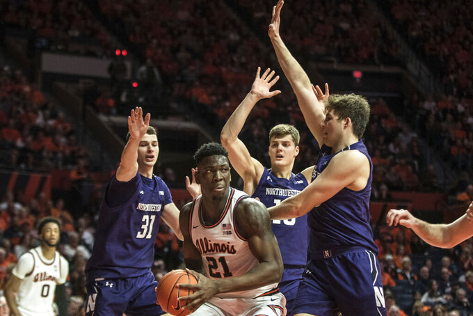 Illinois' Kofi Cockburn (21) faces heavy pressure from Northwestern's Robbie Beran (31) Miller Kopp (10) and Ryan Young (15) in the first half of an NCAA college basketball game, Saturday Jan. 18, 2020, in Champaign, Ill. (AP Photo/Holly Hart)