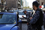 Police officers speak to a driver at a checkpoint while inspecting cars for violating a lockdown to help prevent the spread of the coronavirus, in Beirut Lebanon, Thursday, Jan. 21, 2021. Authorities on Thursday extended a nationwide lockdown by a week to Feb. 8 amid a steep rise in coronavirus deaths and infections that has overwhelmed the health care system. (AP Photo/Bilal Hussein)