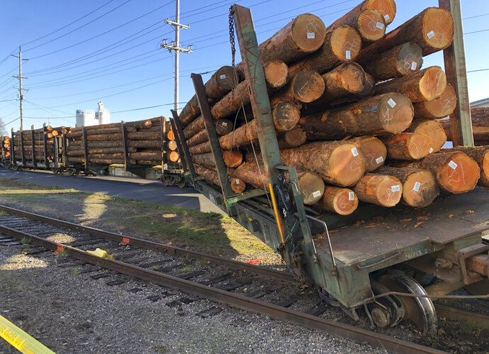A train carrying a load of logs is derailed Wednesday, Dec. 5, 2018, near Salem, Ore., causing authorities to close several roads. The derailment occurred Tuesday night in an industrial area a few blocks north of downtown Salem. Several railroad cars loaded with dozens of heavy logs remained off the tracks Wednesday, but the logs had not spilled off the railroad cars. (AP Photo/Andrew Selsky)