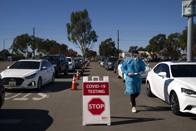 FILE - In this Nov. 16, 2020, file photo, student nurse Ryan Eachus collects forms as cars line up for COVID-19 testing at a testing site set up the OC Fairgrounds in Costa Mesa, Calif. Orange County will provide up to half a million mail-in test kits to residents before the end of the year in the hopes that more testing can help beat back the coronavirus. Orange County will offer the free test kits initially to residents of its two largest cities, Anaheim and Santa Ana. Health officials hope to make the kits available to all of the county's 3 million residents by next month in what could be a massive boost in testing. unemployment rate stubbornly high. (AP Photo/Jae C. Hong, File)
