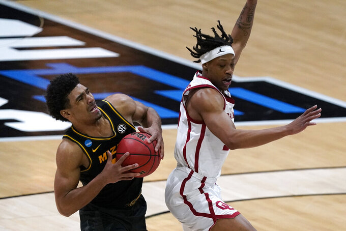 Missouri guard Mark Smith, left, is fouled by Oklahoma guard Alondes Williams, right, during the second half of a first-round game in the NCAA men's college basketball tournament at Lucas Oil Stadium, Saturday, March 20, 2021, in Indianapolis. (AP Photo/Darron Cummings)