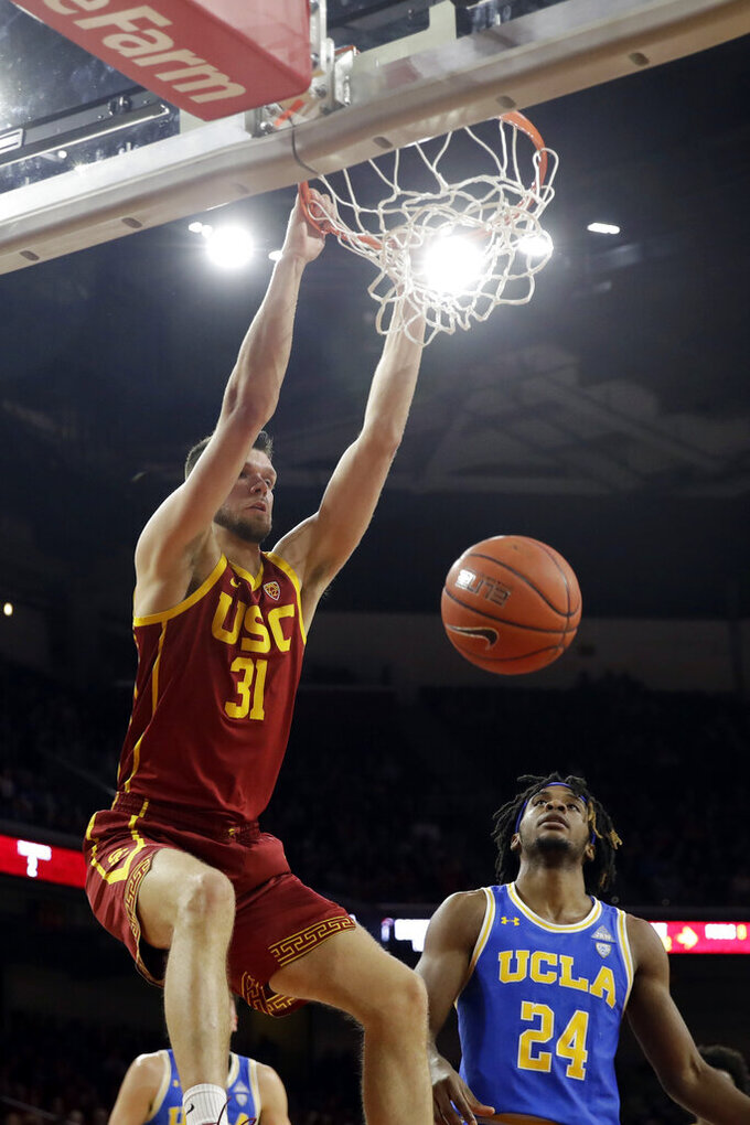 Southern California forward Nick Rakocevic (31) dunks over UCLA forward Jalen Hill (24) during the first half of an NCAA college basketball game Saturday, March 7, 2020, in Los Angeles. (AP Photo/Marcio Jose Sanchez)