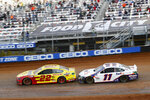 Driver Joey Logano (22) leads Denny Hamlin (11) through Turn 4 during an NASCAR Cup Series auto race, Monday, March 29, 2021, in Bristol, Tenn. (AP Photo/Wade Payne)