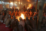 In this Feb. 7, 2019 photo, Hindu holy men perform prayers for becoming Naga Sadhus or naked holy men at Sangam, the confluence of three holy rivers during the Kumbh Mela or pitcher festival in Prayagraj Uttar Pradesh state, India. At every Kumbh, including this year's, thousands of devotees were initiated into the reclusive sect of the Naga Sadhus, naked, ash-smeared cannabis-smoking Hindu warriors and onetime-armed defenders of the faith who for centuries have lived as ascetics in jungles and caves. (AP Photo/ Rajesh Kumar Singh)