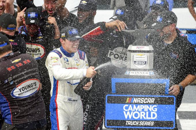 Tate Fogleman sprays a bottle in Victory Lane after winning the NASCAR Truck Series auto race Saturday, Oct. 2, 2021, in Talladega, Ala. (AP Photo/John Amis)